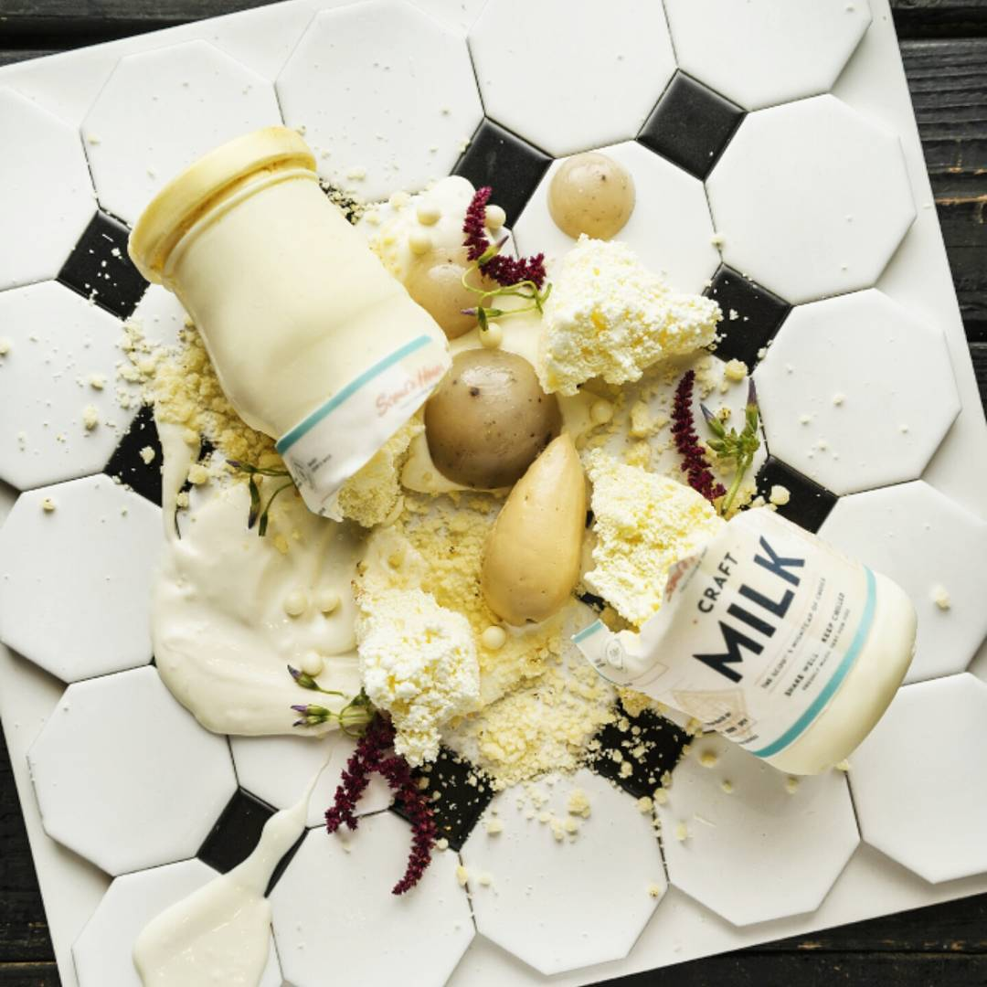 "Spoiled milk and Tonka bean gelee, whipped burnt white cacao ganache, yogurt cheese glaçage, Ricotta cotton cheesecake on white chocolate ""Milk Bottle"